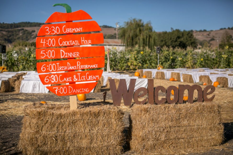 wedding order of events painted on a pumpkin shaped sign on a bale of hay