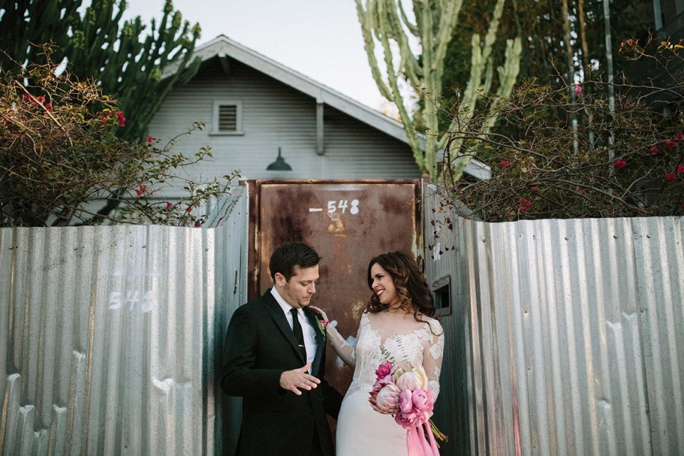 couple smiling and dancing in front of rusty metal gate and corrugated fence