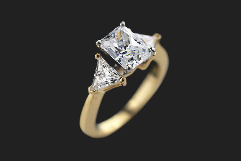 emerald cut ethical diamond engagement ring with gold band and side stone