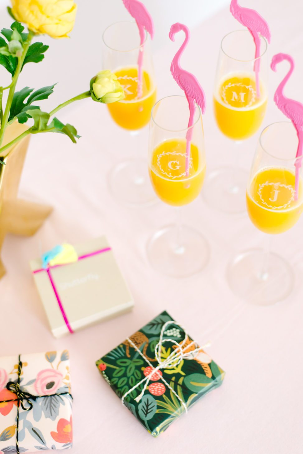 four personalized champagne glasses from Shutterfly with pink flamingo drink stirrers next to a pile of wrapped presents