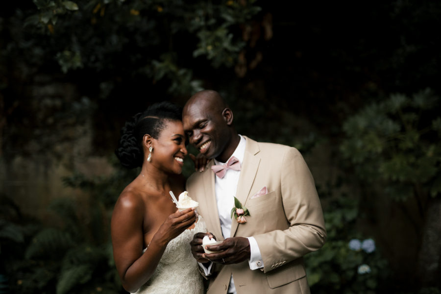 Couple in wedding clothes smiling at each other and eating ice cream