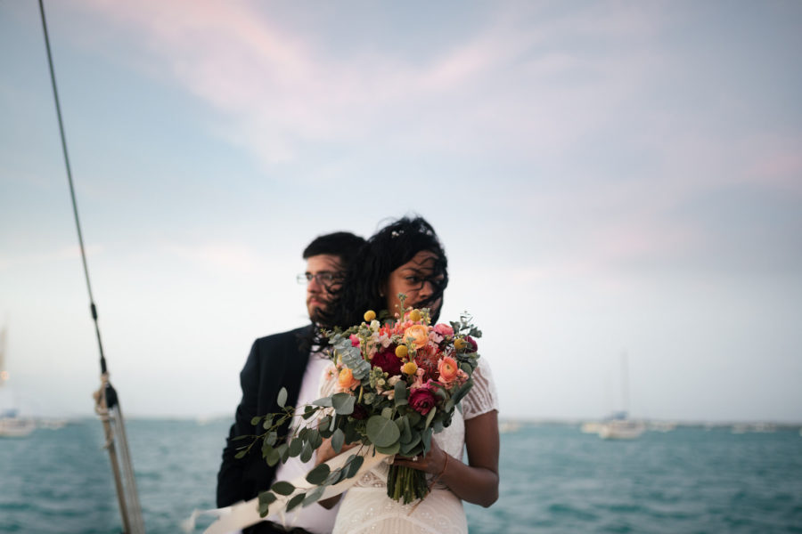 A man and woman stand in front of the ocean as the wind blows