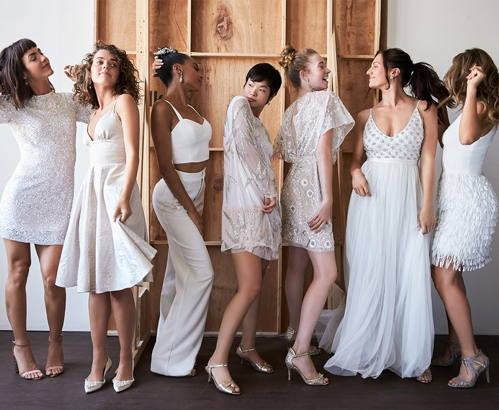 3a607eec3c4 A row of women posing in wedding dresses with five women in short wedding  dresses