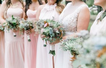 Torsos of bide holding bouquet next to several bridesmaids in pink, holding bouquets
