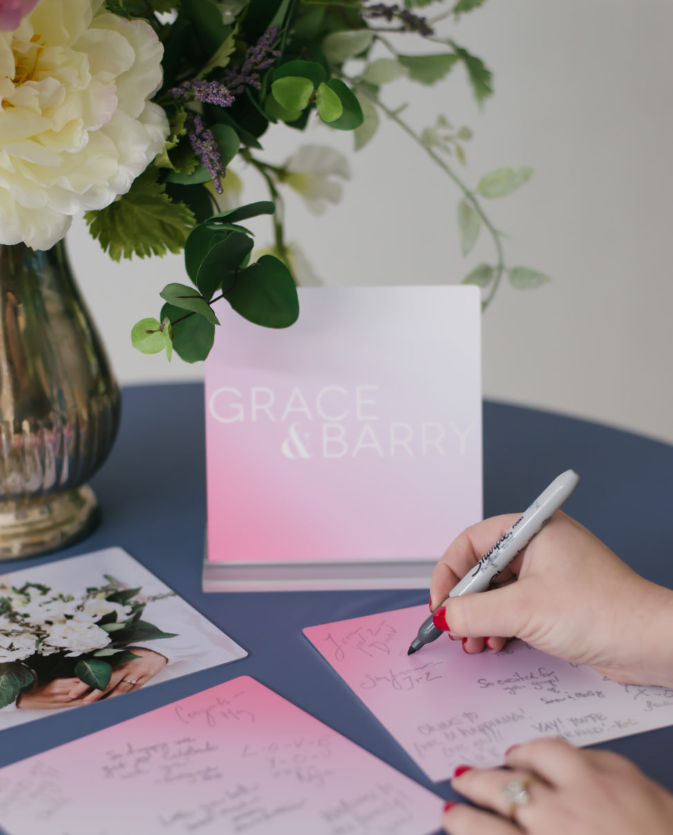 a flower arrangement next to metal prints that a woman is signing
