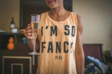 Woman holds glass of champagne while wearing a shirt that reads I'm So Fancy