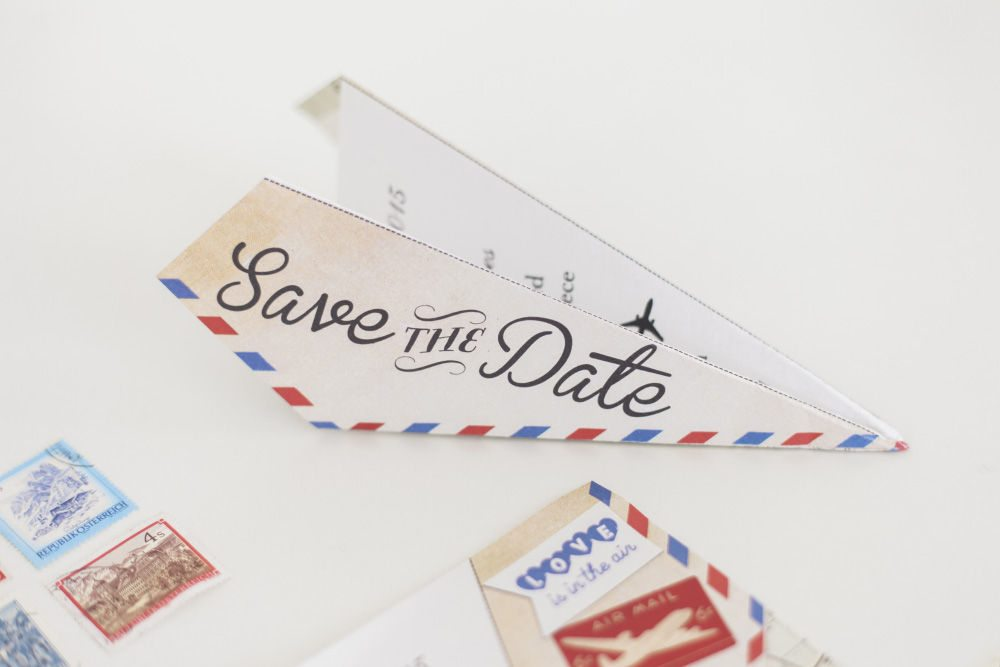 air mail style envelope for a save the date folded into a paper airplane