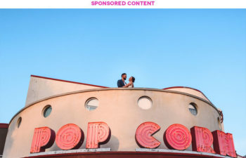 Couple stands above enormous POP CORN sign on top of a building. Sponsored Content.