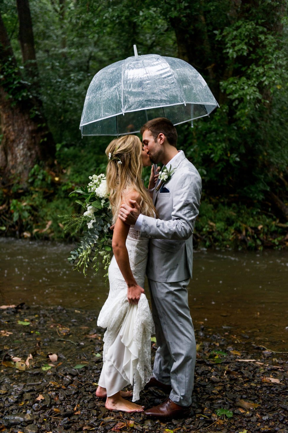 A man and woman kiss in the rain
