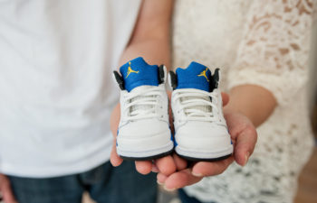 A couple hold a pair of baby shoes
