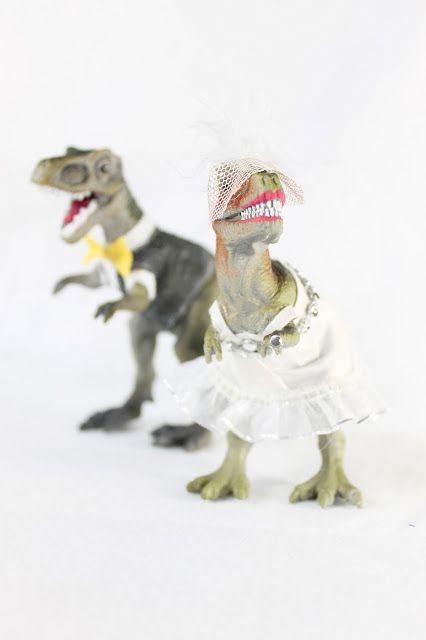t-rex dinosaurs dressed as a bride and groom wedding cake toppers