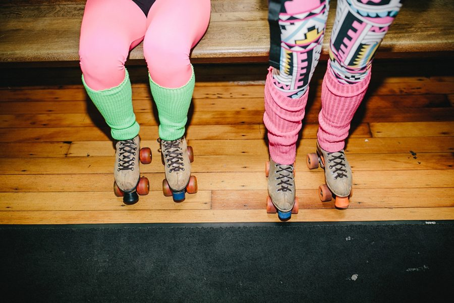 Women's legs with bright tights, leg warmers, and roller skates