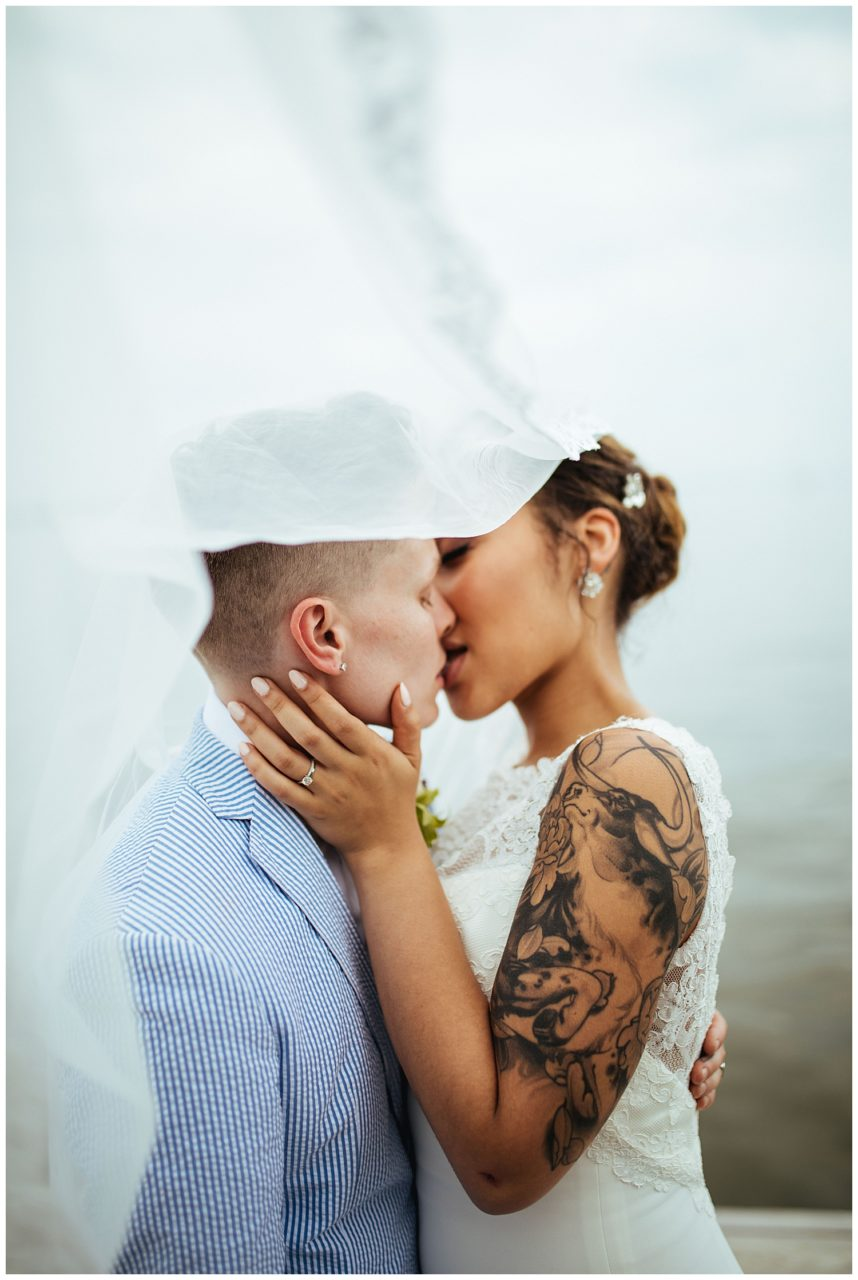 A wedding couple kiss as the wedding veil blows in the wind