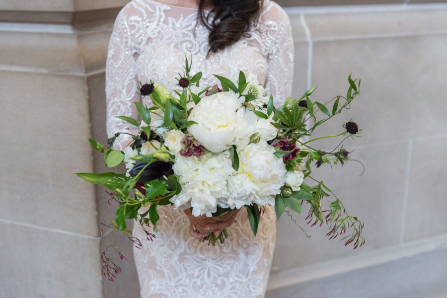 woman in white lace wedding dress holding large white and green bouquet