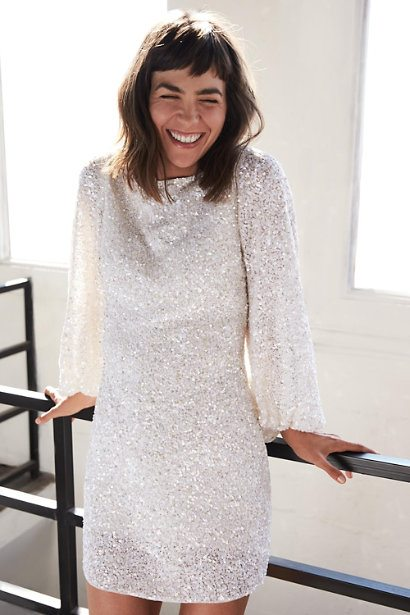 laughing woman in sequined white dress