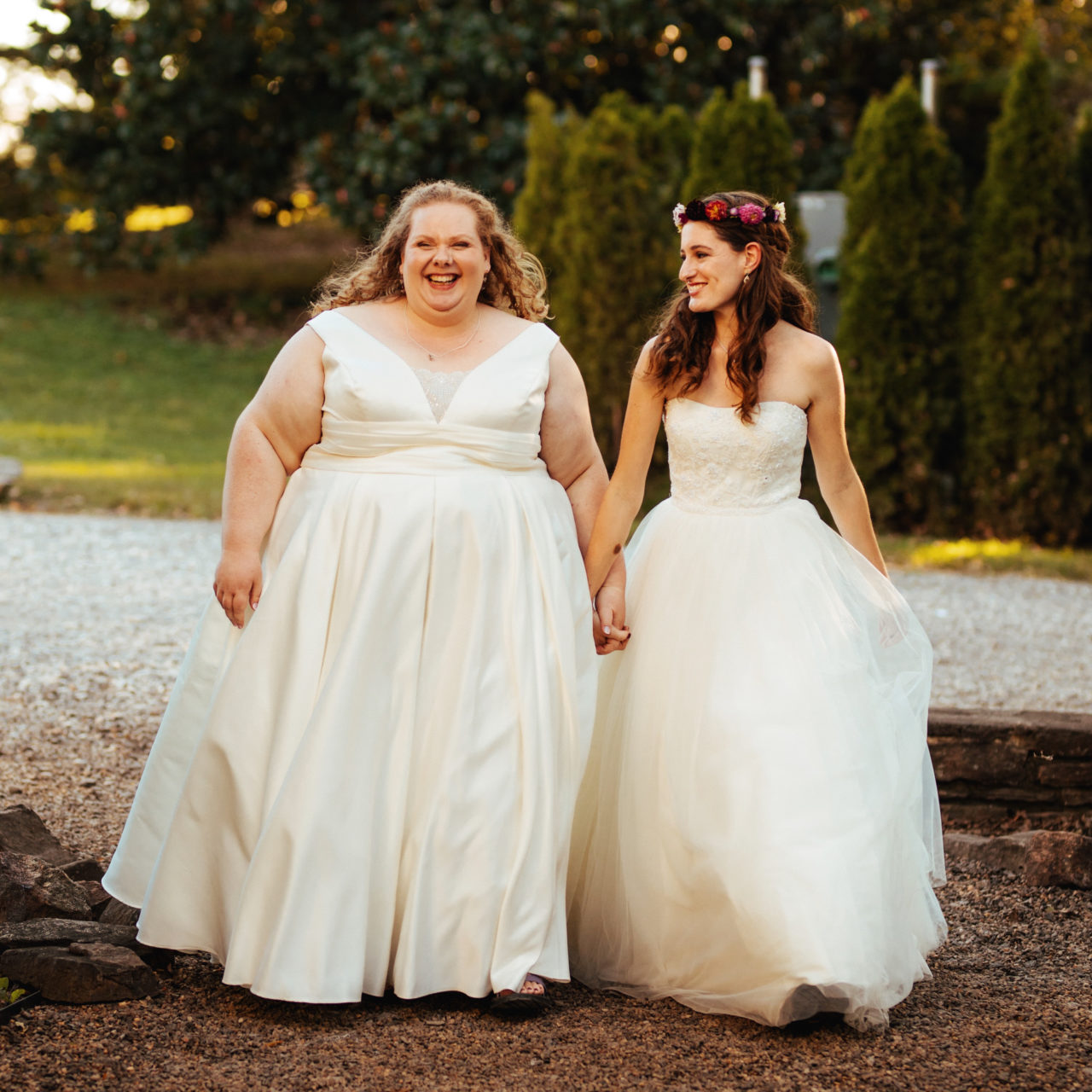 Two women in wedding dresses hold hands and walk together