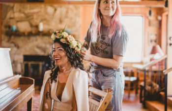 A woman smiles at you as she has her wedding hairstyle done with a flower crown