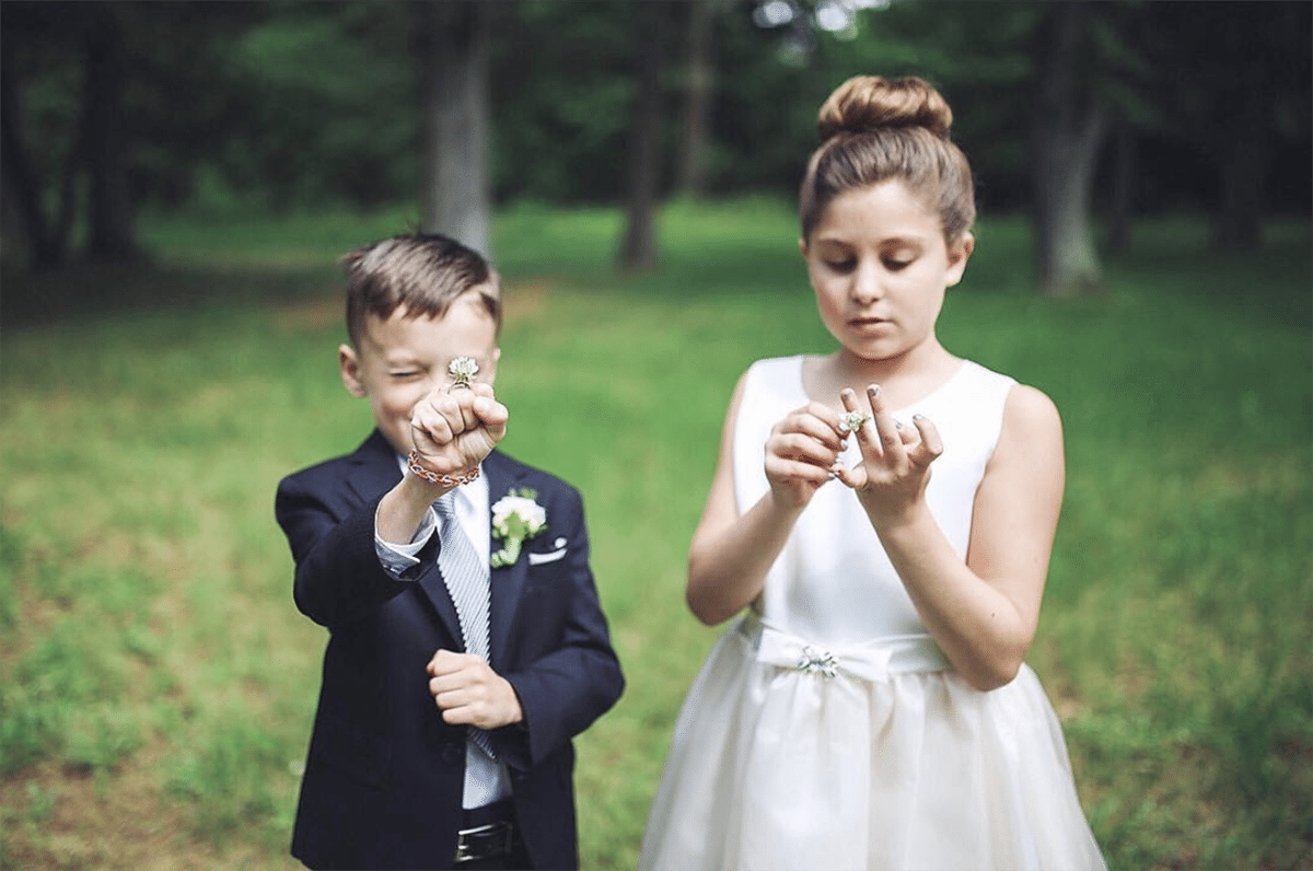 a flower boy and flower girl wear pretend wedding rings made from picked flowers in a wooded field