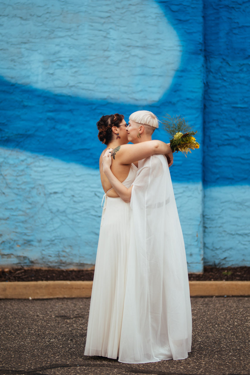 A wedding couple embrace in front of a blue wall