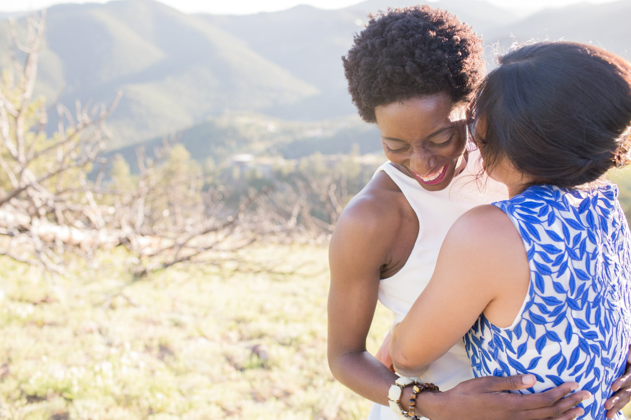 Two women embrace in front of a mountain