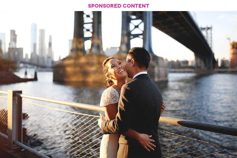 A couple embraces along the water under a bridge