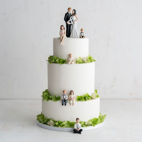 bride and groom holding ampersand cake topper with six children sitting on various tiers of the cake