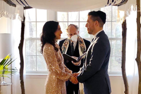 Wedding couple under a chuppah in their living room