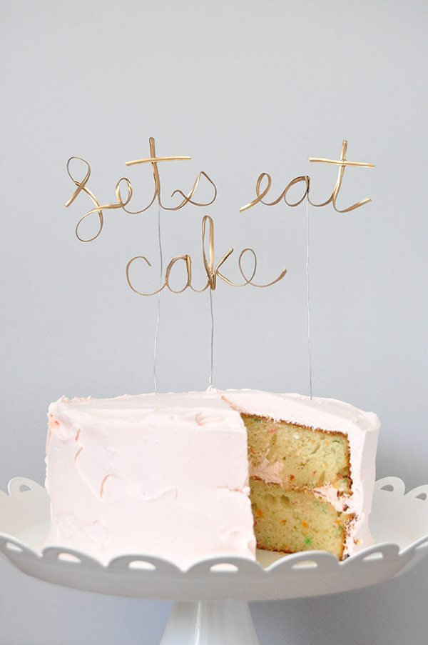 "golden calligraphy cake topper that reads ""Let's eat cake"""