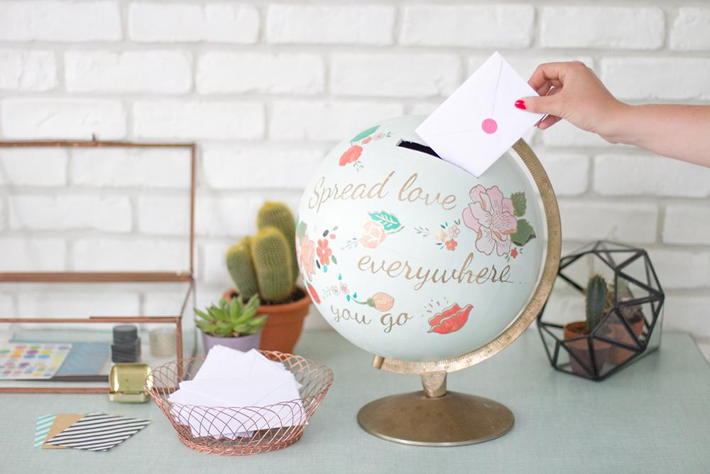 "a globe envelope box that reads ""spread love everywhere you go"""