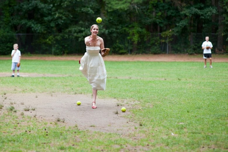 A women wearing a white dress, throws a softball