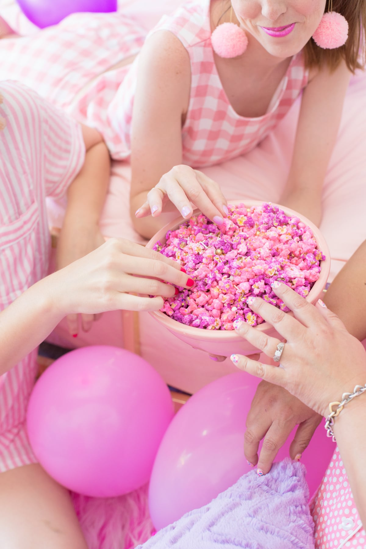 Three women sit on a bed and eat a bowl of pink candy