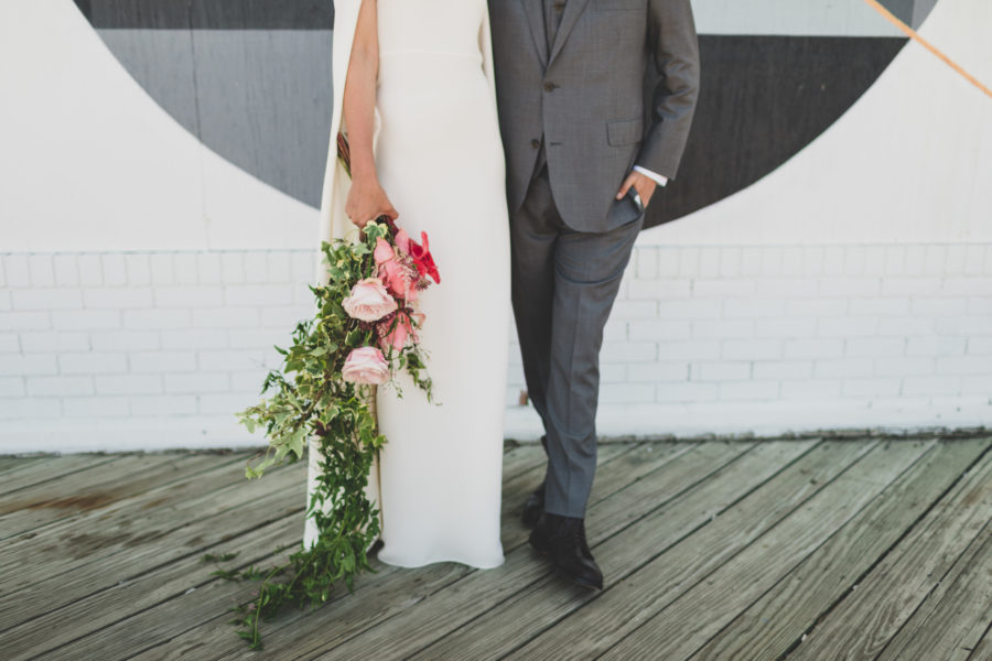 a person in long white dress holds a cascading bouquet alongside as she stands next to a person in a grey suit