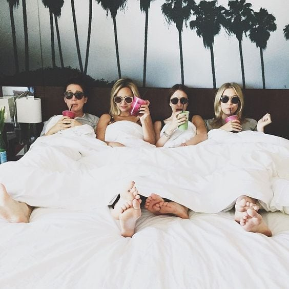 bachelorette party - Four women in a bed with drinks