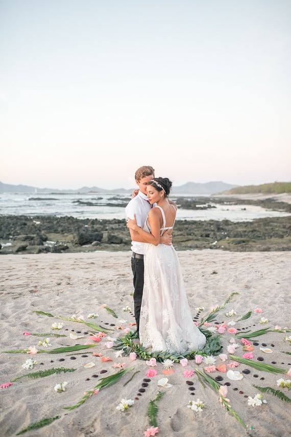 Bride and a groom in a flower mandala at a beach wedding