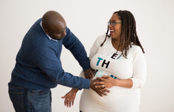 Pregnant woman and her partner hold hands over her belly
