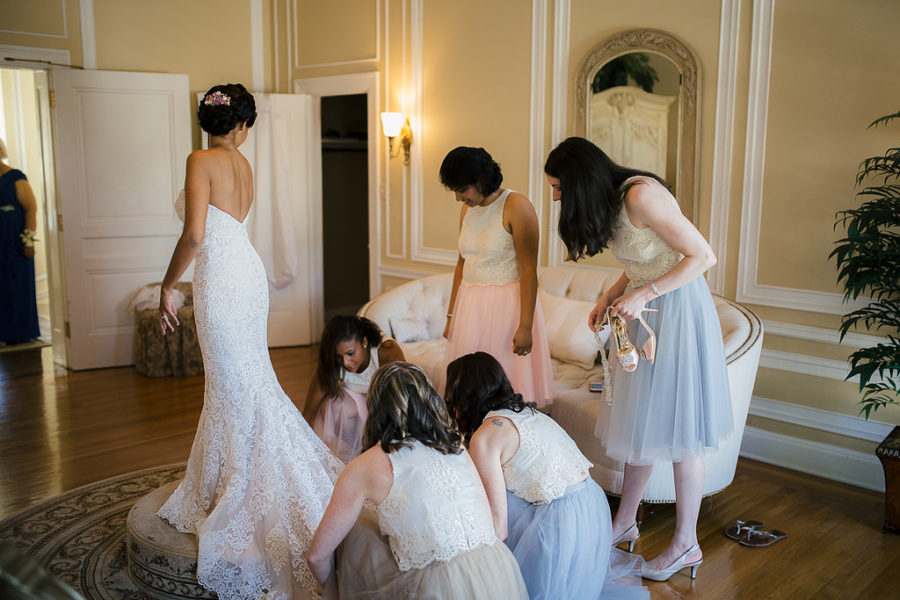 Wedding party adjusting bridal train in front of a mirror