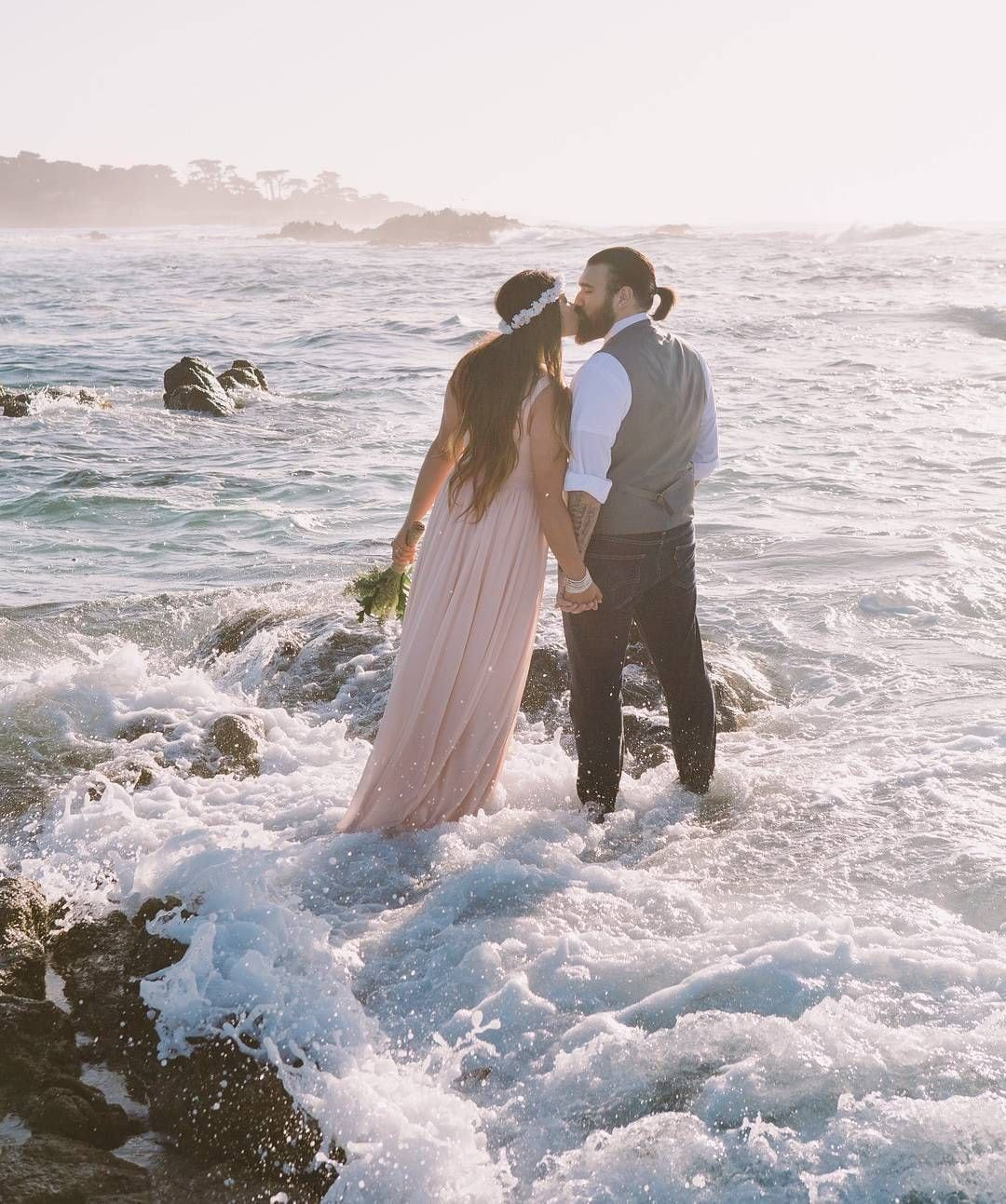 A man and woman kiss while ocean water surrounds them