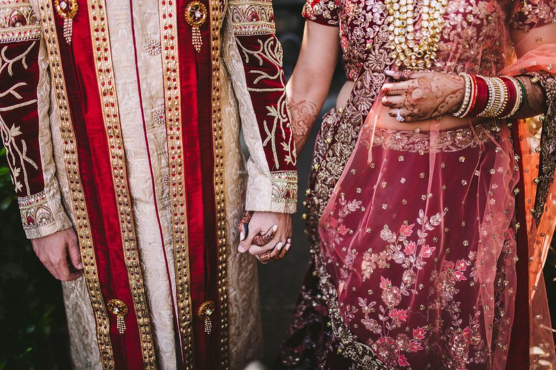 Indian bridal couple holding hands
