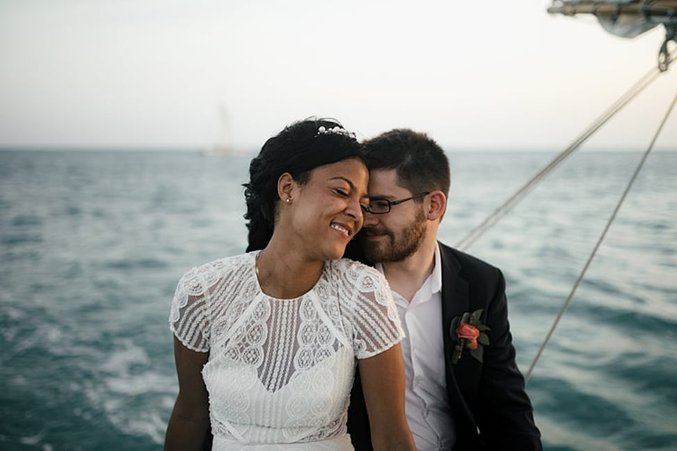 Two people cuddle together while sitting on a boat