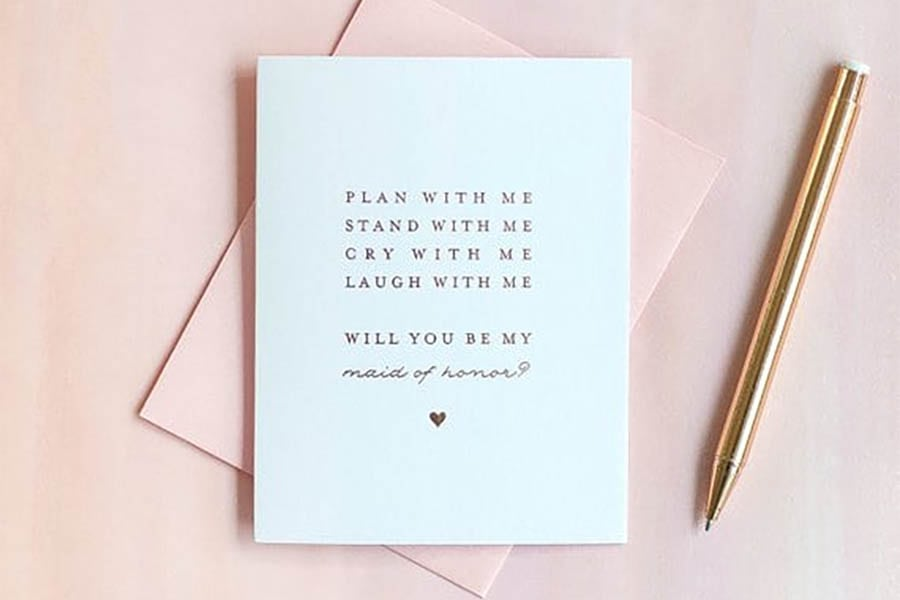 """Notecard that reads: """"Plan with me, stand with me, cry with me, laugh with me. Will you be my maid of honor?"""" on a pink envelope next to a gold pen."""