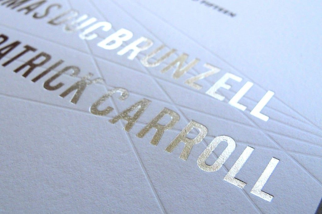 detail of letterpress invite with silver foil and graphic lines