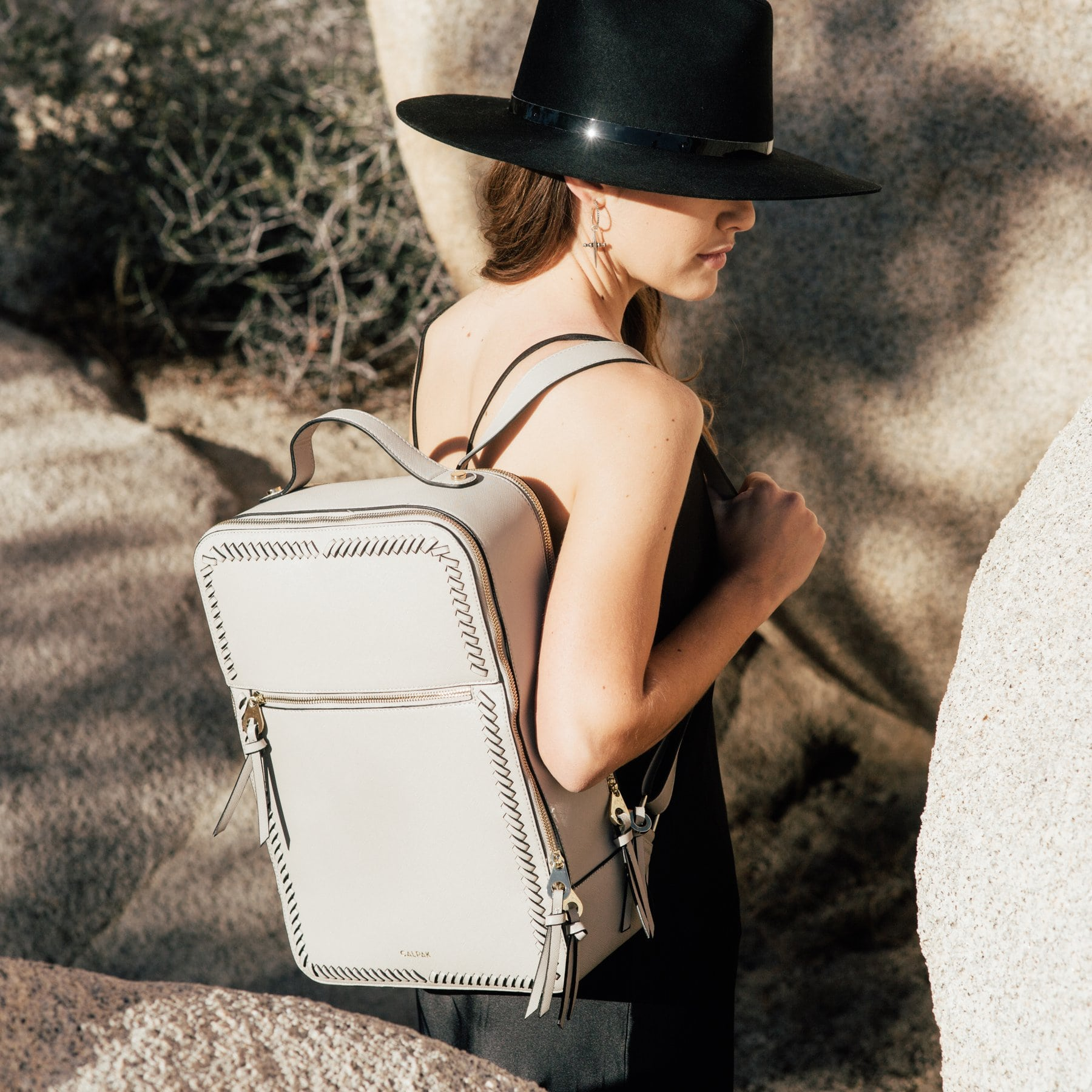 A woman stands in between boulders wearing a black hat and white backpack