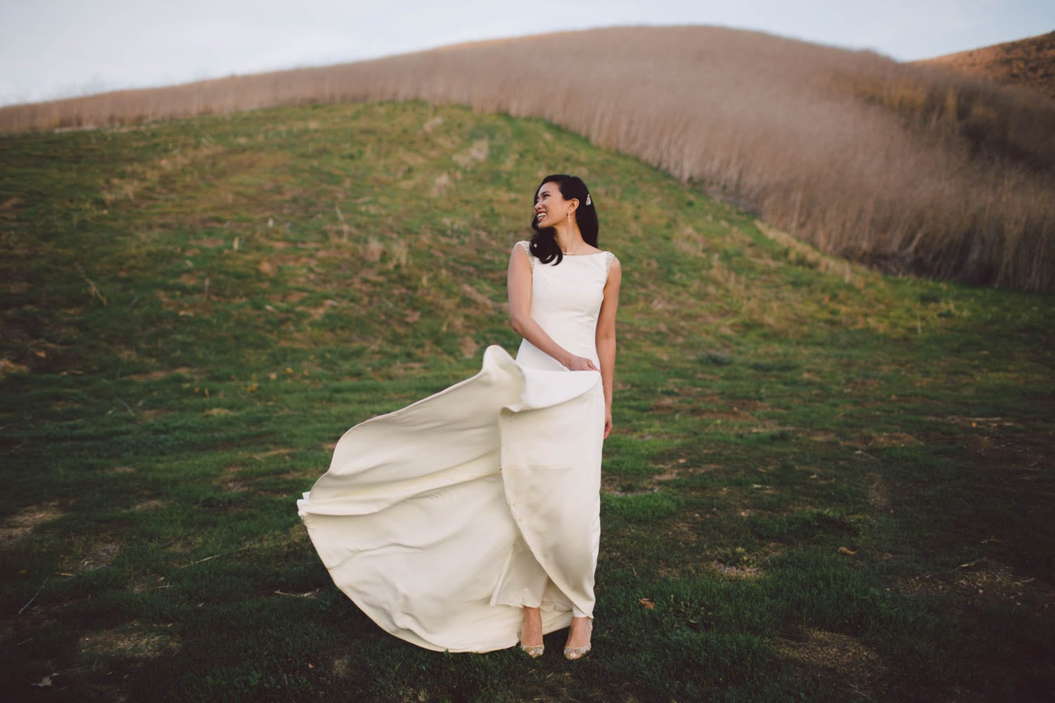 A woman stands on a mountainside in her wedding dress.