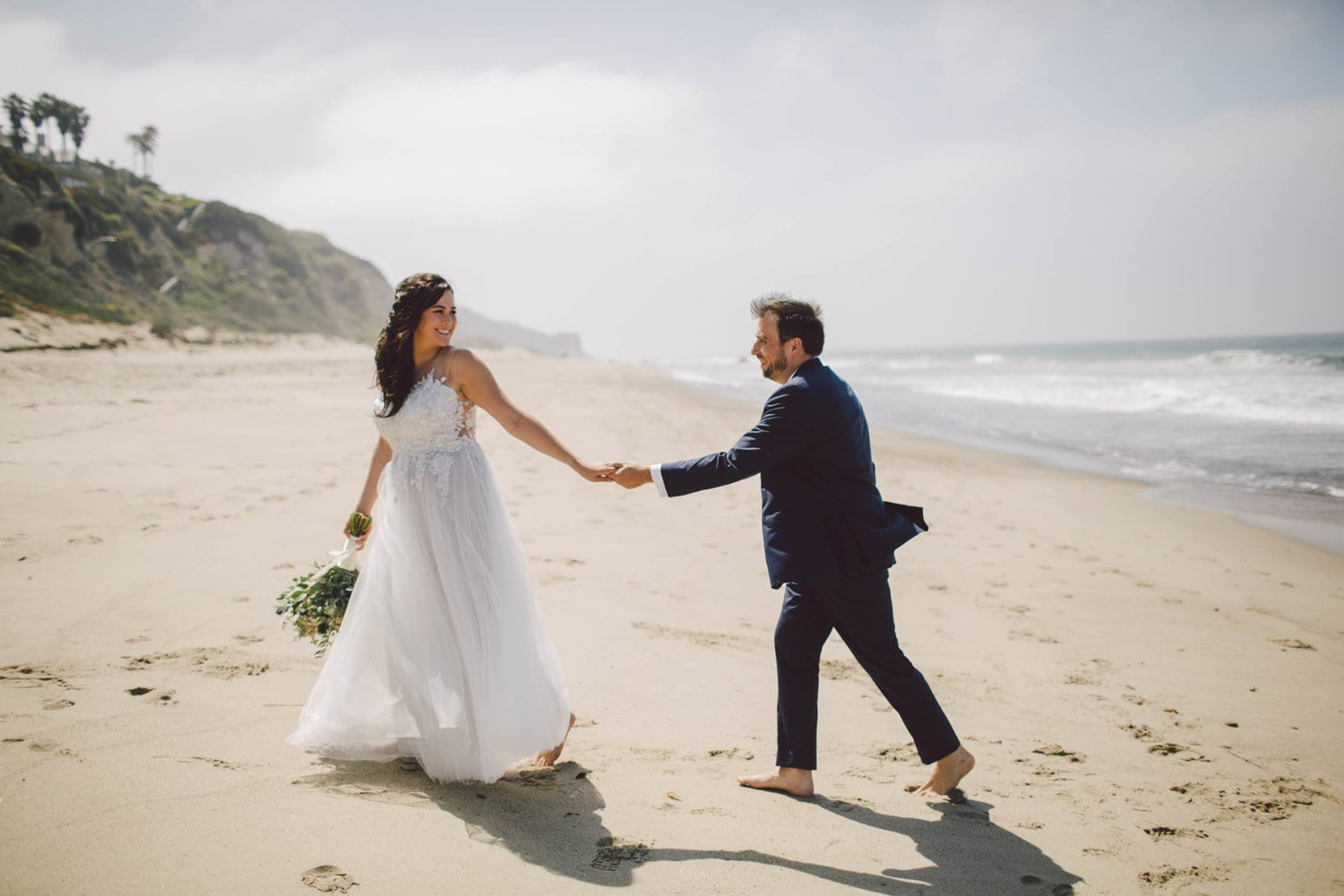 A couple walk together, at the beach.
