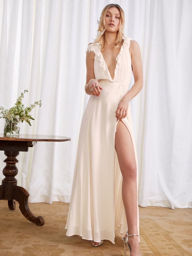 A woman wears a cream wrap-style dress with a plunging v, loose ruffle accents on the neckline and a high slit