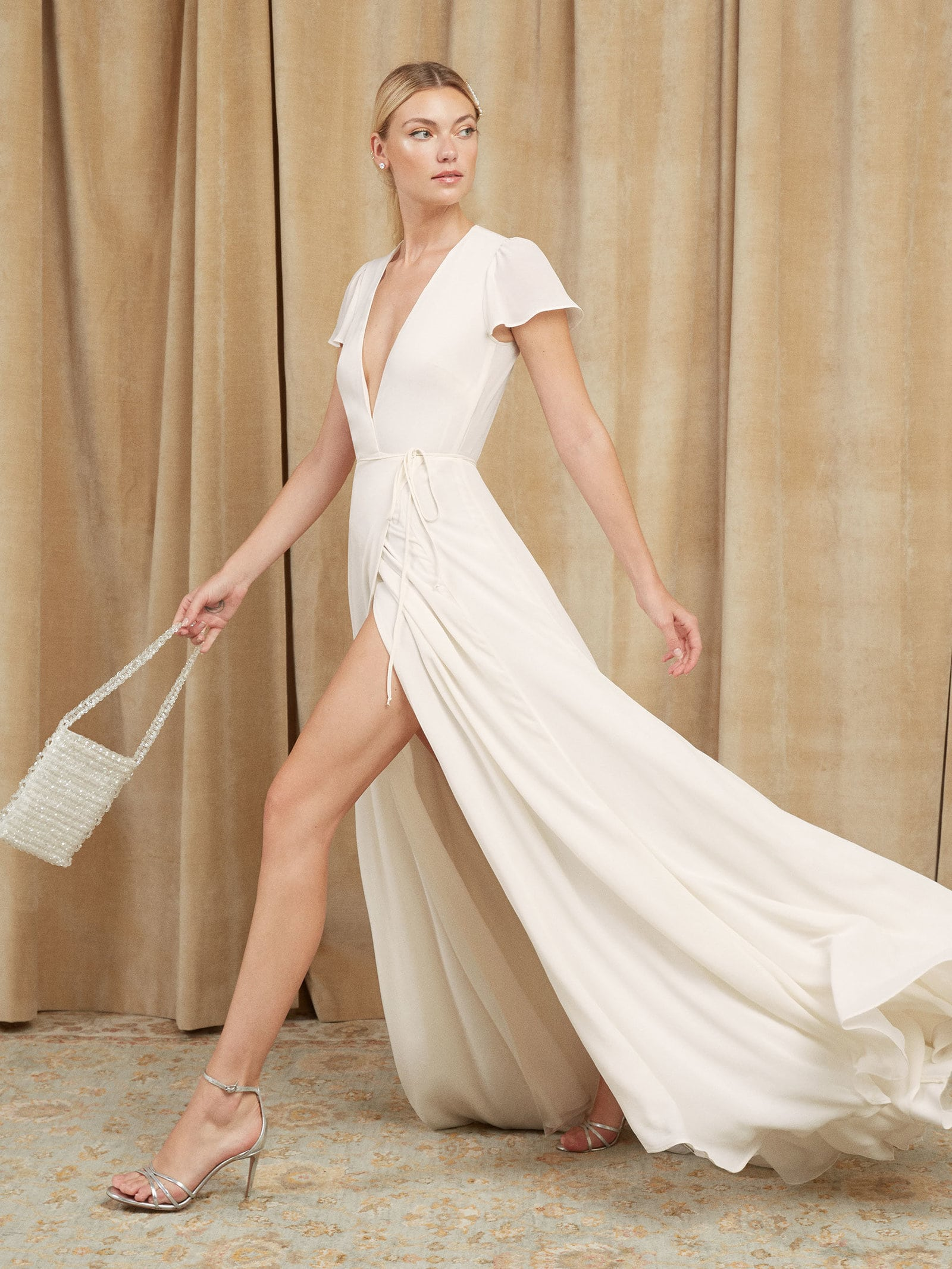 A woman wears a white wrap-style dress with a plunging neckline, flutter short sleeves and a full, flowing skirt