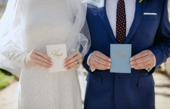 Wedding Vows held by a bride in a white dress and veil and groom in a blue suit
