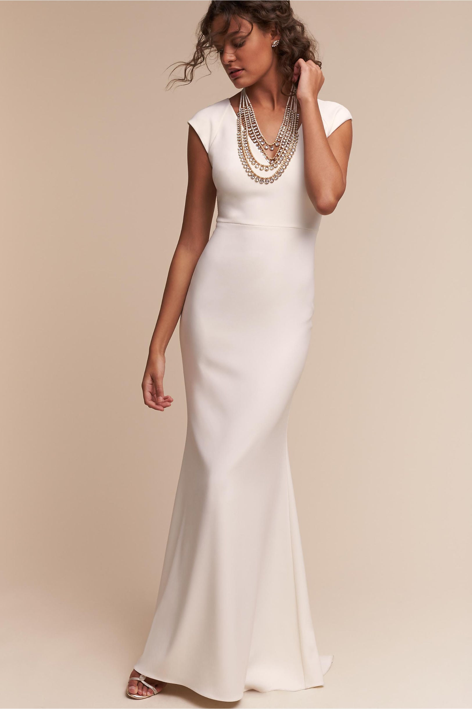 A woman wears a v-neck white column dress with cap sleeves and a large statement necklace