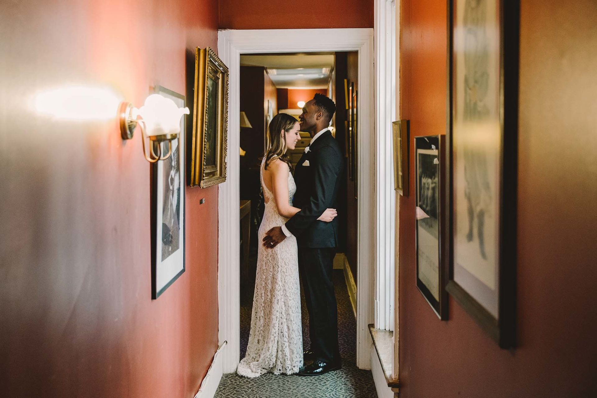 a couple stands in embrace, smiling, in a hallway. Rachel Couch for Pop! Wed Co.