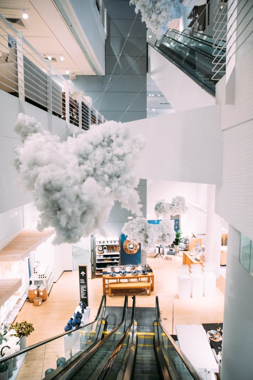 The inside of a Crate and Barrel store with a giant cloud installation over the escalator for crate and barrel san francisco private registry event with a practical wedding
